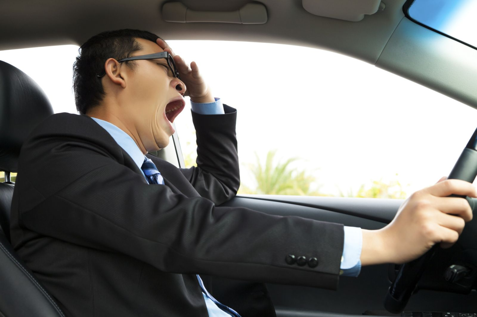 man driving while yawning