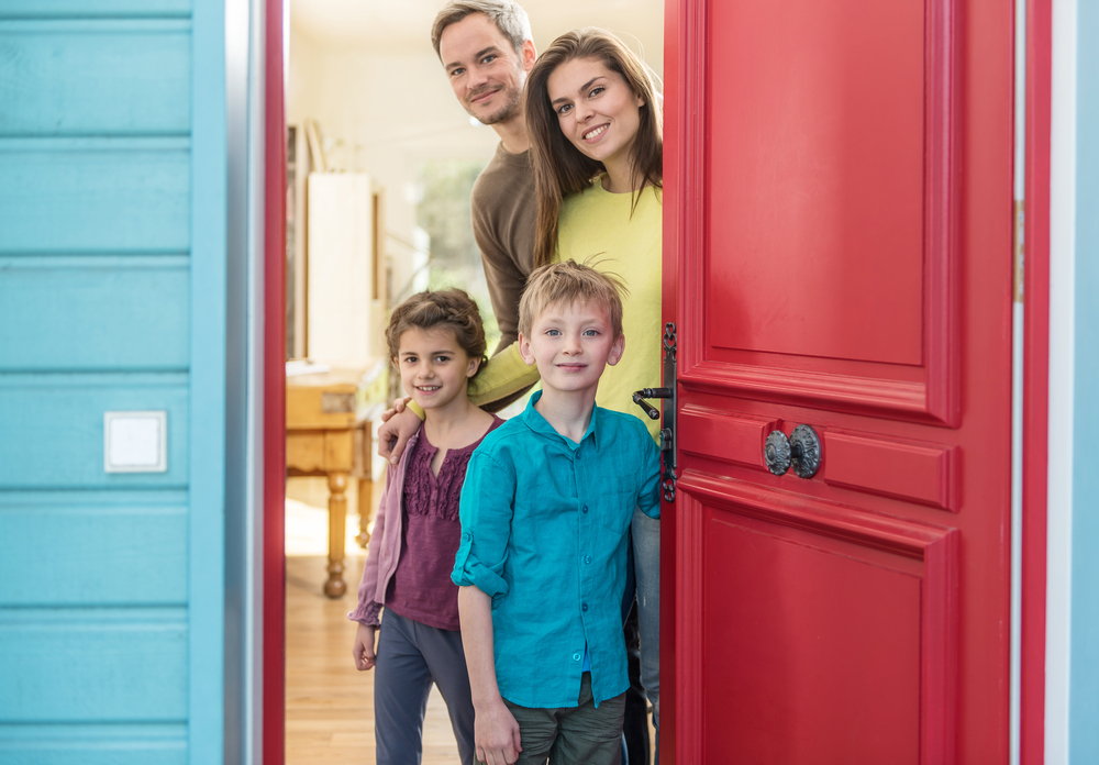 family greeting guest at door