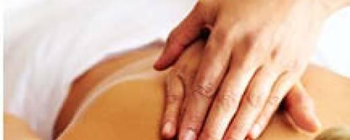 therapist hand massaging client's shoulder