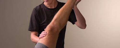 therapist massaging and stretching leg