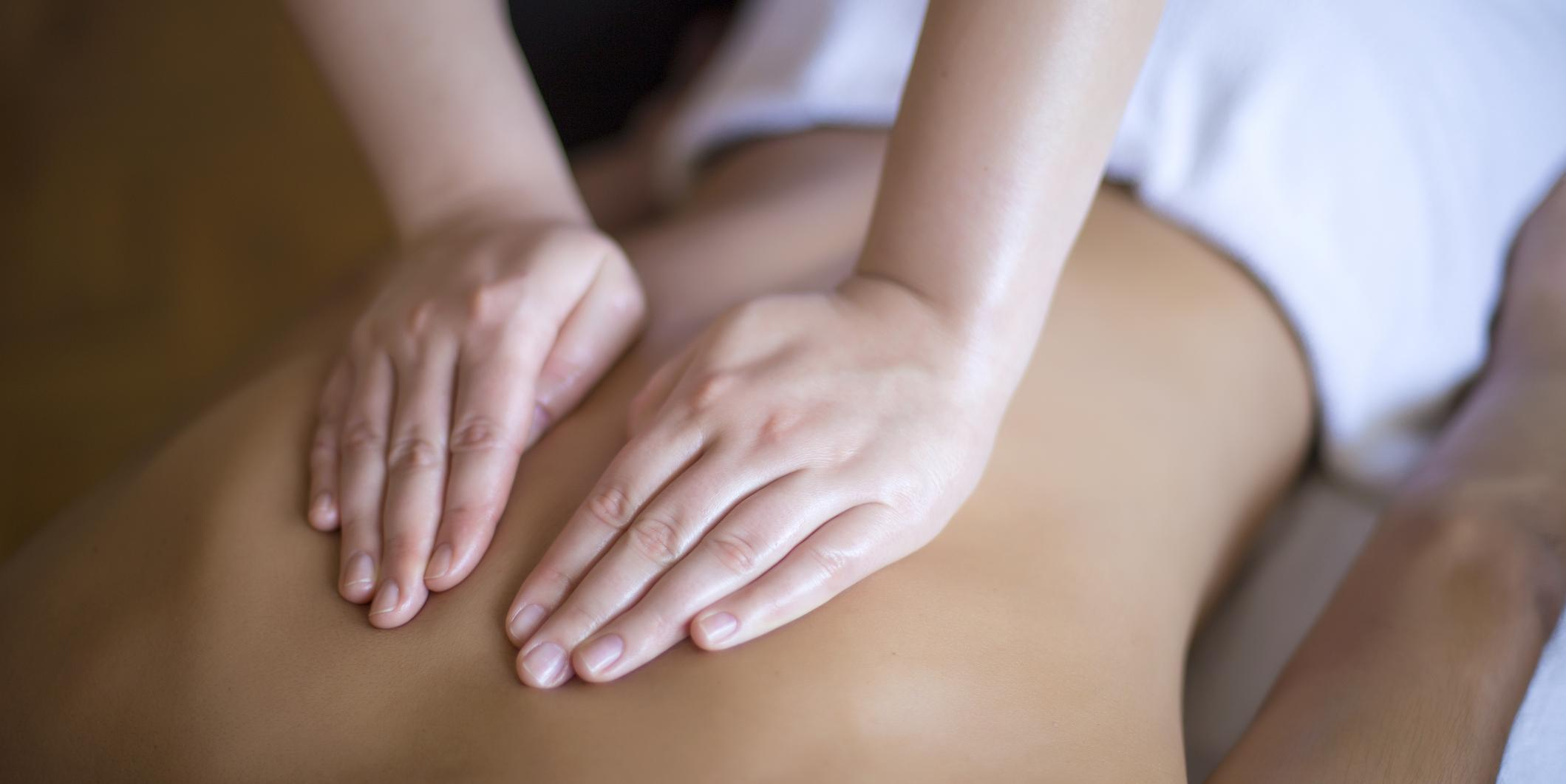 massage therapist hands on someone's back