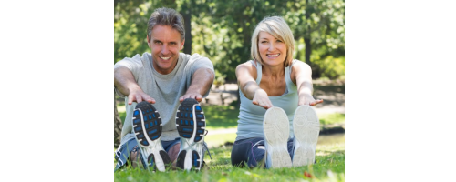 image of a couple stretching, sitting & touching their toes, smiling