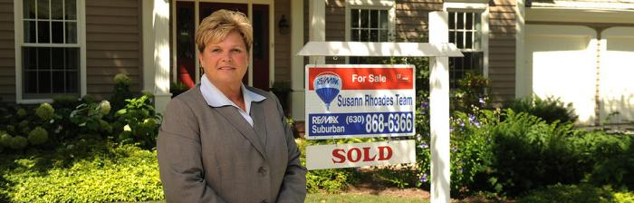 Susann Rhoades standing by for sale sign Logo