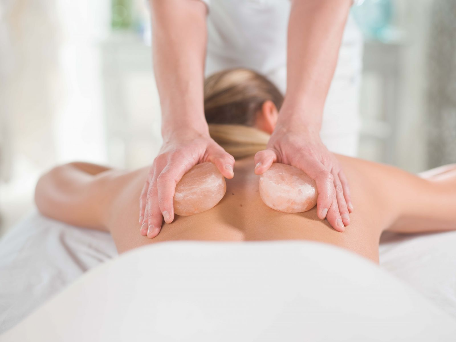 woman receiving himalayan salt stone massage