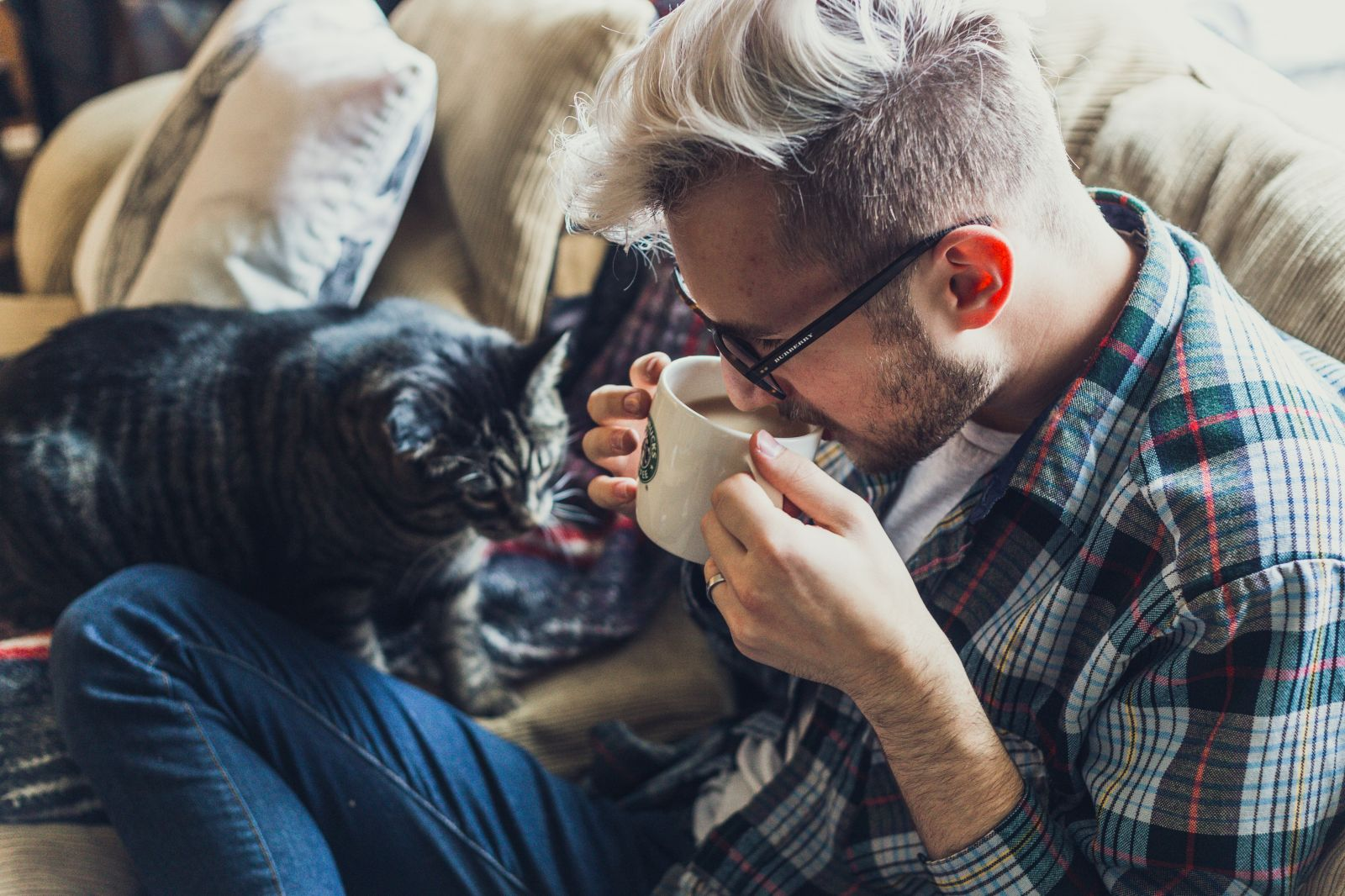 man drinking coffee on couch with cat